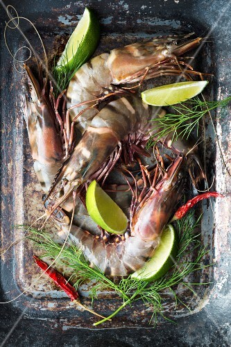Raw king prawns with dill, chilli and lime wedges