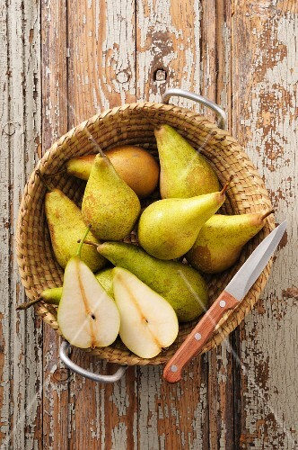 A basket of pears on a rustic wooden table