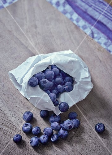 Blueberries on a wooden table with a paper bag