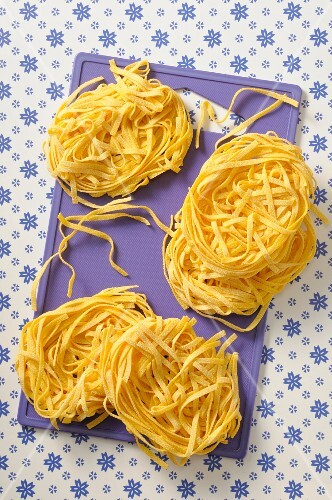 Homemade tagliatelle on a chopping board (seen from above)