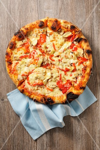 Pizza with tomatoes and artichokes on a wooden surface