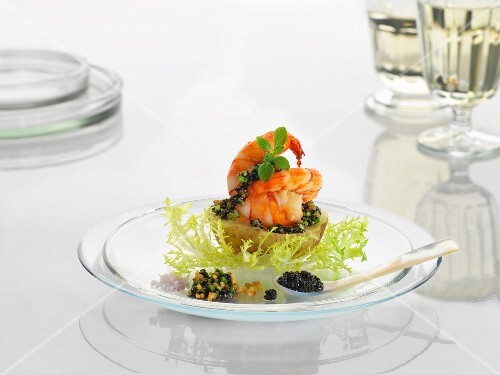 A new potato with prawns and caviar on a glass plate