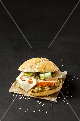 An Alpine burger with Leberkäse (beef and pork meatloaf) and lettuce on a dark surface