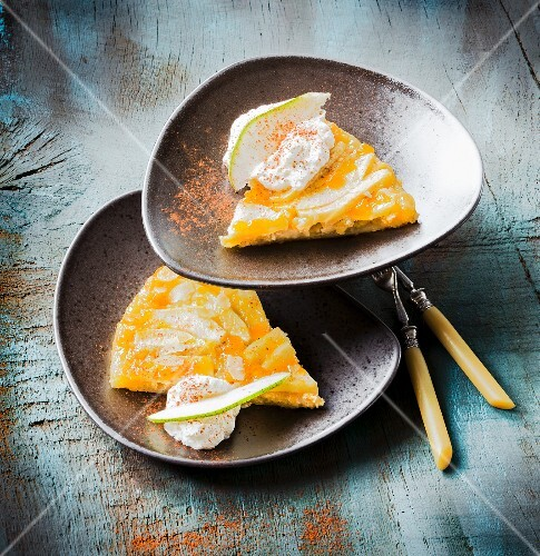 Two slices of pear tart with cream on a plate