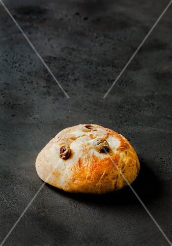 A burger bun with olives on a dark surface