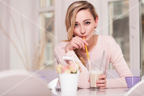 A young woman sitting at a table in a cafe drinking a latte macchiato with a straw