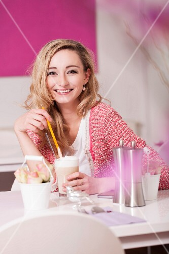Young woman sitting at café table drinking latte macchiato