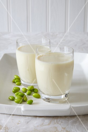Two glasses of vegan soya milk and green soya beans