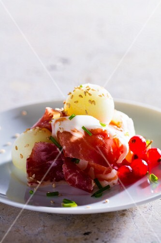 Prosciutto with melon balls and sesame seeds