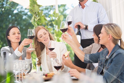 Young women tasting red wine at a table outside