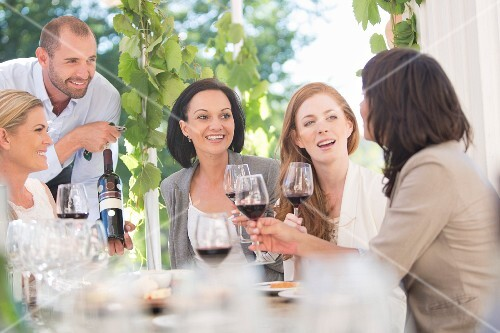 Young women sitting at a table outside at a wine tasting session with the waiter presenting a bottle of wine