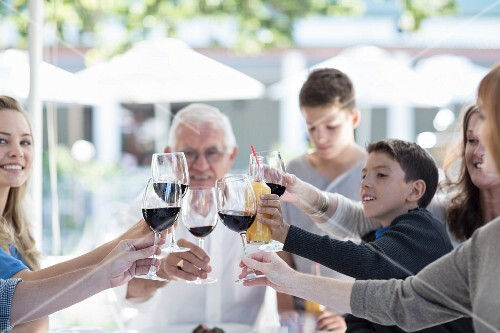 A family eating together at a terrace table: raising a toast with glasses of red wine and lemonade