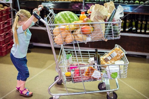 A little girl pushing a full shopping trolley through a supermarket
