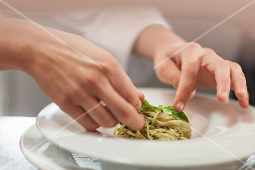 A chef garnishing a spaghetti dish with basil leaves