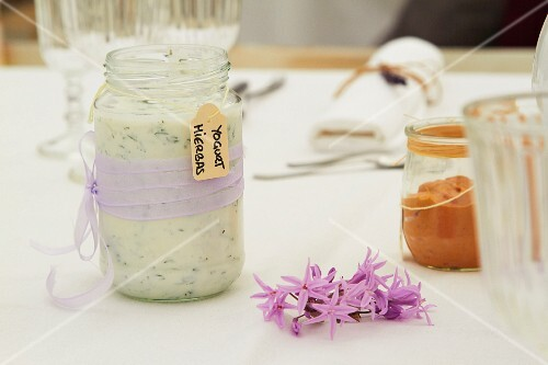 Herb yoghurt in a glass with a purple ribbon on a table