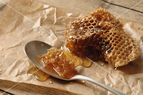 A wild bee honeycomb on parchment paper and a spoon