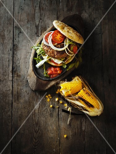 A hamburger with tomato salsa and grilled corn cobs