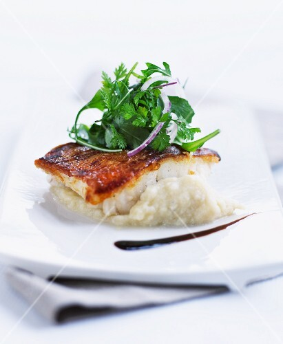 Crispy fish fillet on a bed of mashed potatoes and celery