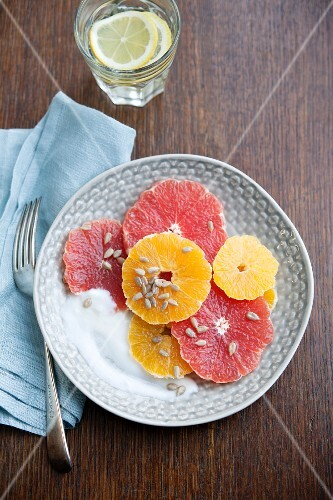 Citrus salad with pink grapefruit, oranges, sunflower seeds and yoghurt