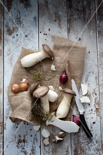 King trumpet mushrooms with onions and herbs on a small sack (seen from above)