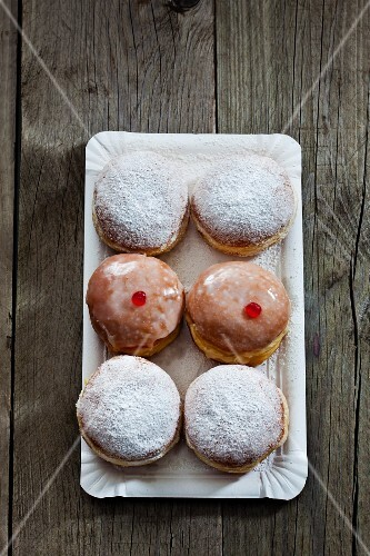Six doughnuts, iced and dusted with icing sugar, on a paper tray (seen from above)