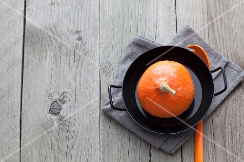 A whole raw Hokkaido pumpkin in a pan (seen from above)