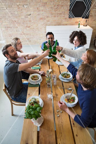 Friends eating together: raising a toast with beer bottles