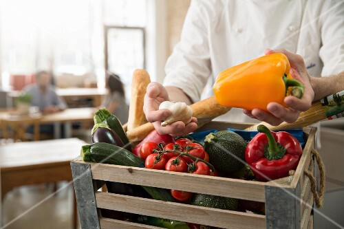 A chef checking a crate of fresh vegetables