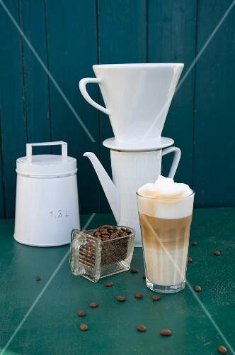 Arrangement of coffee featuring a vintage coffee tin, a filter, a joke, coffee beans and a latte macchiato