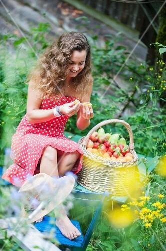 Young woman with basket of fruit in cottage garden (Altenmarkt-Zauchensee, Salzburger Land, Austria)