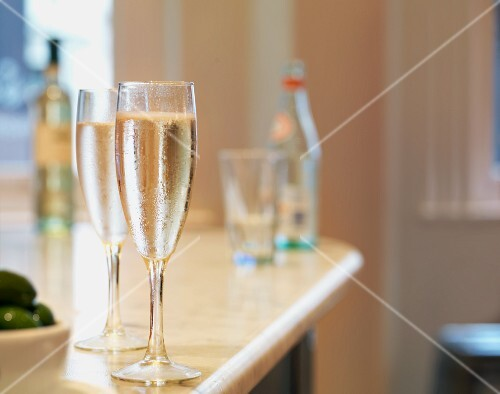 Two glasses of sparkling wine on a bar