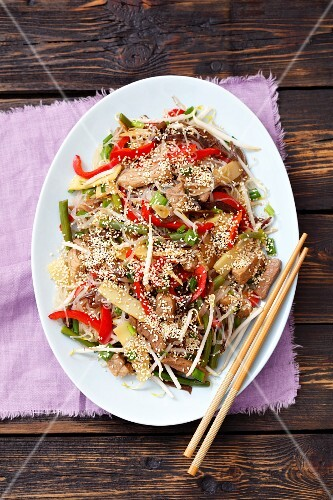 Noodle salad with fried pork, bamboo shoots, peppers, mushrooms, beans and sesame seeds (China)