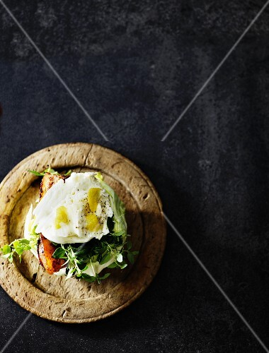 A poached egg with bacon and herbs served in an iceberg lettuce leaf