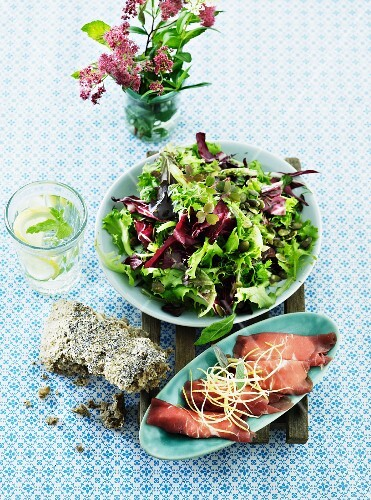 Green salad with carpaccio rolls and bread