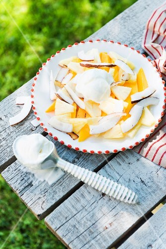 Yellow summer fruit salad with mango, ice cream and coconut