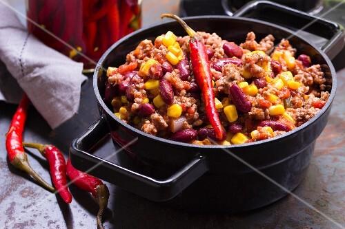 Chili con Carne mit Chilischoten in schwarzem Emailletopf