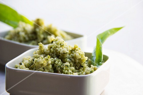 White quinoa as a salad with herbs in white dishes