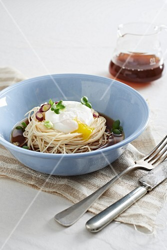 Coffee and mushrooms soup with noodles and a poached egg