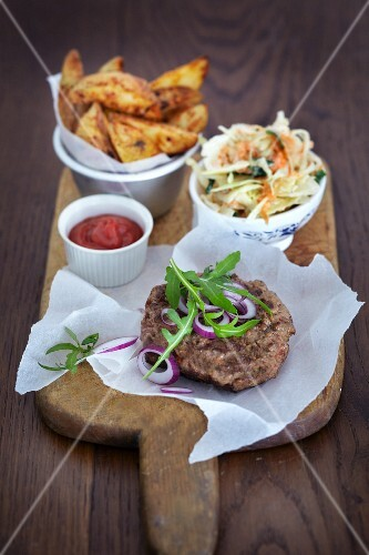 A hamburger with potato wedges and coleslaw