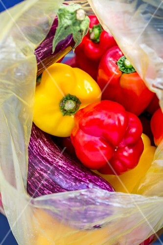 Fresh peppers and aubergines in a plastic bag