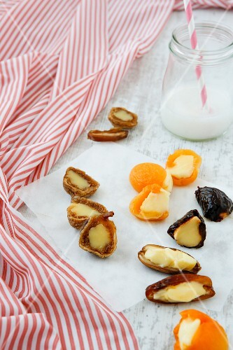 Tried to date and apricots filled with cream cheese with a glass of milk and a straw in the background