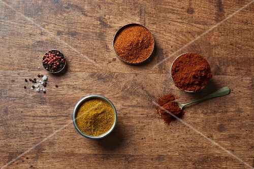 Various spices on a wooden surface (seen from above)