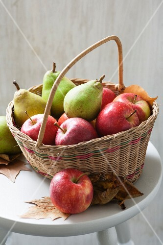 Apples and pears in a basket with autumn leaves