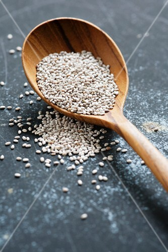 White chia seeds on a wooden spoon