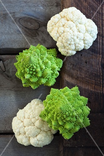 White cauliflower and Romanesco broccoli on a wooden crate