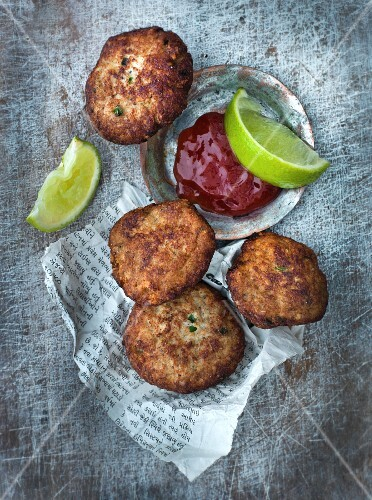 Fish cakes with a tandoori sauce and limes