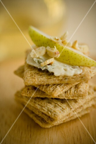 A stack of crackers topped with cheese, pear and almonds