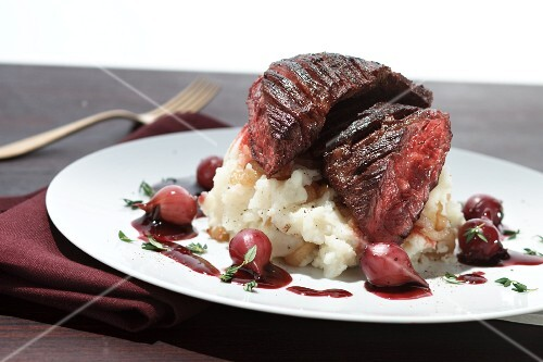Beefsteak on mashed potatoes with red wine onions