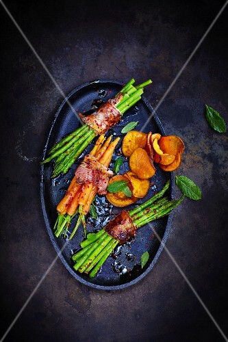 Asparagus and carrots wrapped in bacon with vegetable crisps