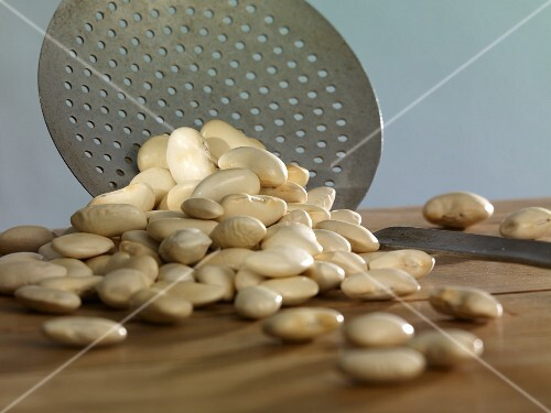 Large white beans with a draining spoon
